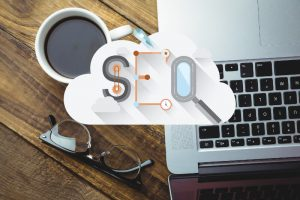 an image of a coffee cup next to a laptop's keyboard with SEO written across it
