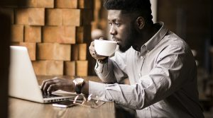 man drinking coffee engaging in online shopping, which is a form of e-commerce